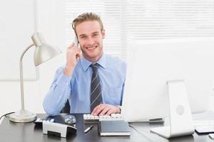 glimlachende zakenman die en bij zijn bureau werkt telefoneert