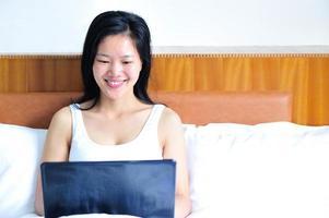 glimlachende vrouw die op het bed leunt met haar notitieboekjecomputer foto