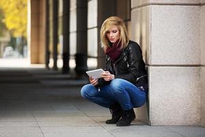 jonge mode vrouw met behulp van tablet-computer aan de muur foto