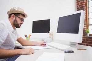 casual ontwerper tekenen achter zijn bureau