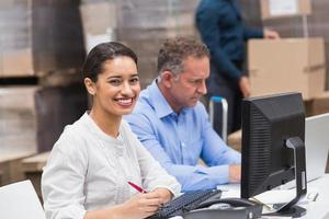 twee managers werken op laptop aan balie