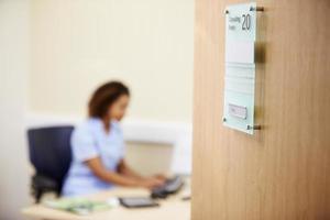 vrouwelijke verpleegster die bij bureau in bureau werkt foto