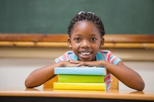 lachende leerling zit aan haar bureau foto
