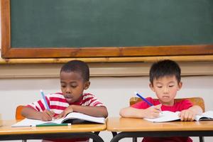 schattige leerlingen schrijven aan balie in klas foto