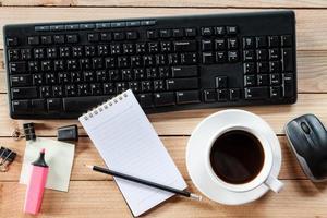 werkplek met notitieboek, potlood, toetsenbord, muis en kopje koffie foto