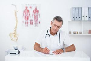 arts die op klembord bij zijn bureau schrijft foto