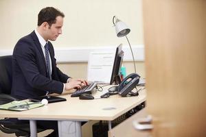 mannelijke adviseur werken bij balie in kantoor foto