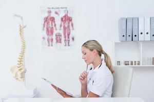 arts die op klembord bij haar bureau schrijft foto