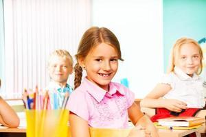 schoolmeisje en andere leerlingen zitten aan een bureau foto