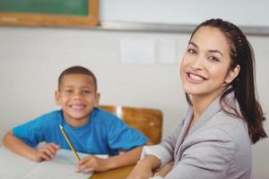 lachende leraar en haar leerling zitten aan de balie foto