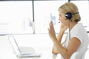 zakenvrouw zitten aan de balie in kantoor met behulp van laptop foto