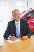 geconcentreerde verkoper die op klembord achter zijn bureau schrijft foto