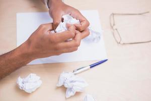handen die documenten op bureau verfrommelen foto