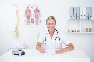 glimlachende arts die op klembord bij haar bureau schrijft foto