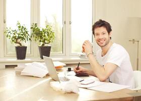 zelfverzekerde glimlachende mens die bij bureau werkt foto