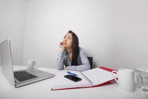 doordachte zakenvrouw zitten aan de balie in kantoor foto