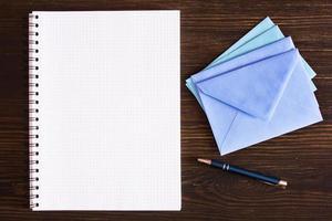 Kladblok, pen en enveloppen op houten bureau. foto