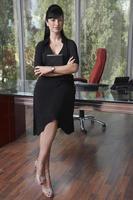 jonge zakenvrouw zittend op balie in kantoor