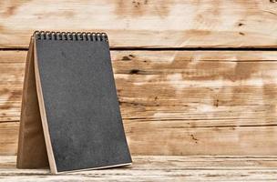 lege bureaukalender op oude houten tafel foto