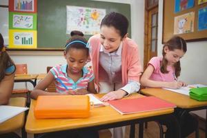 leerling en leraar aan de balie in de klas foto