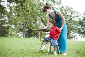 kleine jongen en vrouw aan balie buitenshuis foto