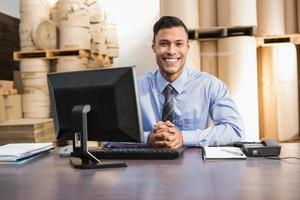 lachende magazijnbeheerder met laptop aan balie