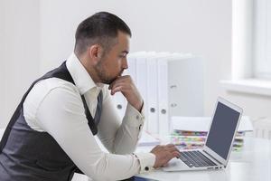 jonge zakenman die bij laptop op bureau gebruikt foto