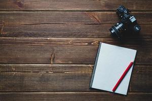 notebook en vintage camera op het bureau foto