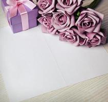 lege kaart met bloemen en cadeau foto
