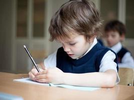 ijverige student zit aan bureau, klaslokaal foto