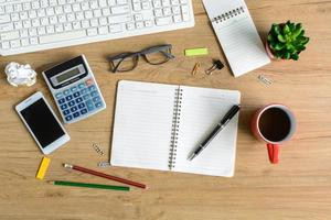 kantoorbenodigdheden en kopje koffie op Bureau foto