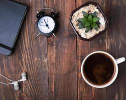 koffie, wekker, vetplant en koptelefoon op tafel foto