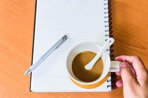man hand en koffie op houten achtergrond foto