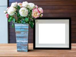lege zwarte afbeeldingsframe en bloemen vaas op houten bureaublad foto