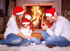 gelukkige familie bij open haard foto