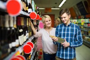 familie die wijn kiest bij voedselwinkel foto