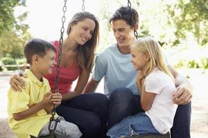 familie zittend op de schommel in de speeltuin foto