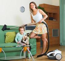 gezin schoonmaken huis met stofzuiger foto