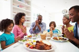multi generatie Afro-Amerikaanse familie thuis bidden