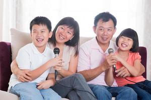 Aziatische familie van vier zingende karaoke foto