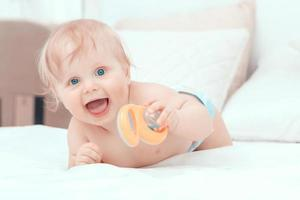 kleine baby tot op het bed en lachend foto