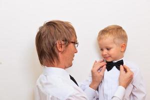 vader die zijn zoon helpt om bowtie, concept van de familiebijstand te binden foto