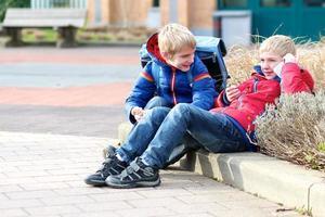 twee jongens met smartphone na school foto