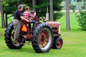grootvader en kleinzoon rijden in een vintage tractor foto