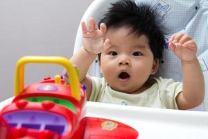 Aziatische babymeisje op hoge stoel foto