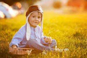 schattige jongen, spelen met vliegtuig op zonsondergang in het park foto