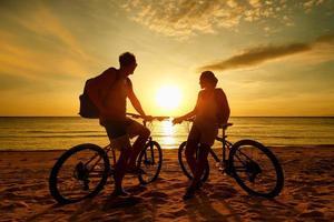 paar toeristen met fietsen kijken naar zonsondergang. silhouet mensen