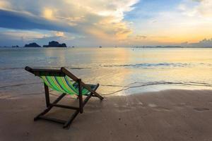 ligstoelen staan op het strand bij zonsondergang