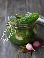 glazen pot met verse zoutarme komkommers foto