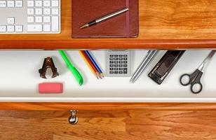 georganiseerde desktop en open lade met houten vloer eronder foto